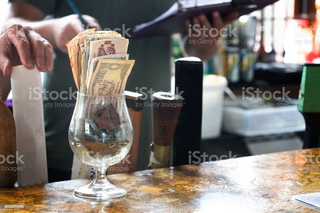 Glass with banknotes and coins. stock photo
