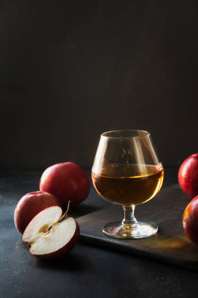 Glass with Calvados brandy and red apples on black. Glass with Calvados brandy and red apples on black. Close up. calvados stock pictures, royalty-free photos & images