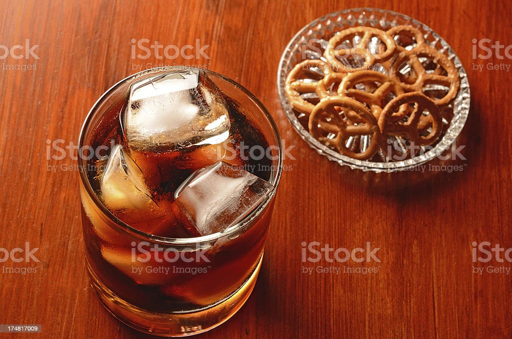 Glass with coke on ice and pretzel royalty-free stock photo