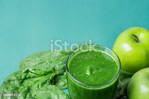 istock Glass with Green Fresh Raw Smoothie from Leafy Greens Vegetables Fruits Apples Bananas Kiwi on Scattered Spinach Leaves. Healthy Lifestyle Detox Vitamins Energy Concept. Copy space 1059614114