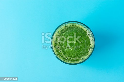 istock Glass with Green Fresh Raw Smoothie from Leafy Greens Vegetables Spinach Fruits Apples Bananas Kiwi on Mint Blue Background. Healthy Lifestyle Detox Vitamins Energy Concept. Copy space Minimalist 1059614128