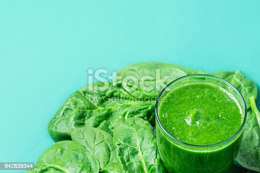 istock Glass with Green Fresh Smoothie from Leafy Greens Vegetables Fruits. Apples Bananas Kiwi Zucchini Scattered Spinach Leaves on Turquoise Background. Healthy Lifestyle Detox Vitamins. Copy Space 942839344