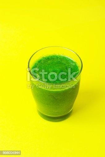 istock Glass with Green Fresh Smoothie from Leafy Greens Vegetables Fruits Bananas Kiwi Cucumber Apple Spinach on Yellow Background. Healthy Lifestyle Detox Vitamins Alkaline Food. Copy Space Top View 956004944