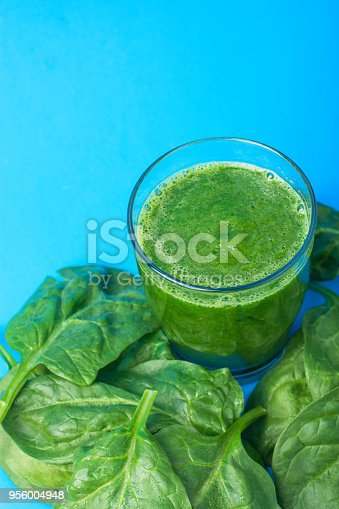 istock Glass with Green Fresh Smoothie from Leafy Greens Vegetables Fruits Bananas Kiwi Cucumber Apple. Scattered Spinach Leaves on Blue Background. Healthy Lifestyle Detox Vitamins. Copy Space Top View 956004948