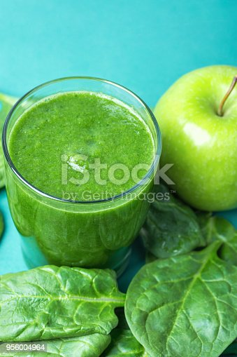 istock Glass with Green Fresh Smoothie from Leafy Greens Vegetables Fruits Bananas Kiwi Cucumber. Scattered Spinach Leaves Apple on Turquoise Background. Healthy Lifestyle Detox Vitamins. Copy Space 956004964