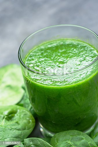 istock Glass with green raw smoothie from vegetables fruits apples bananas kiwi zucchini on spinach leaves. Healthy plant based diet detox vitamins energy concept vertical 1169530632