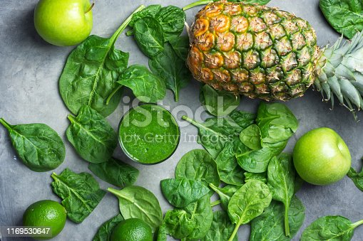 istock Glass with green raw smoothie with ingredients vegetables spinach fruits pineapple citrus apples on dark background. Healthy plant based diet detox vitamins energy concept 1169530647