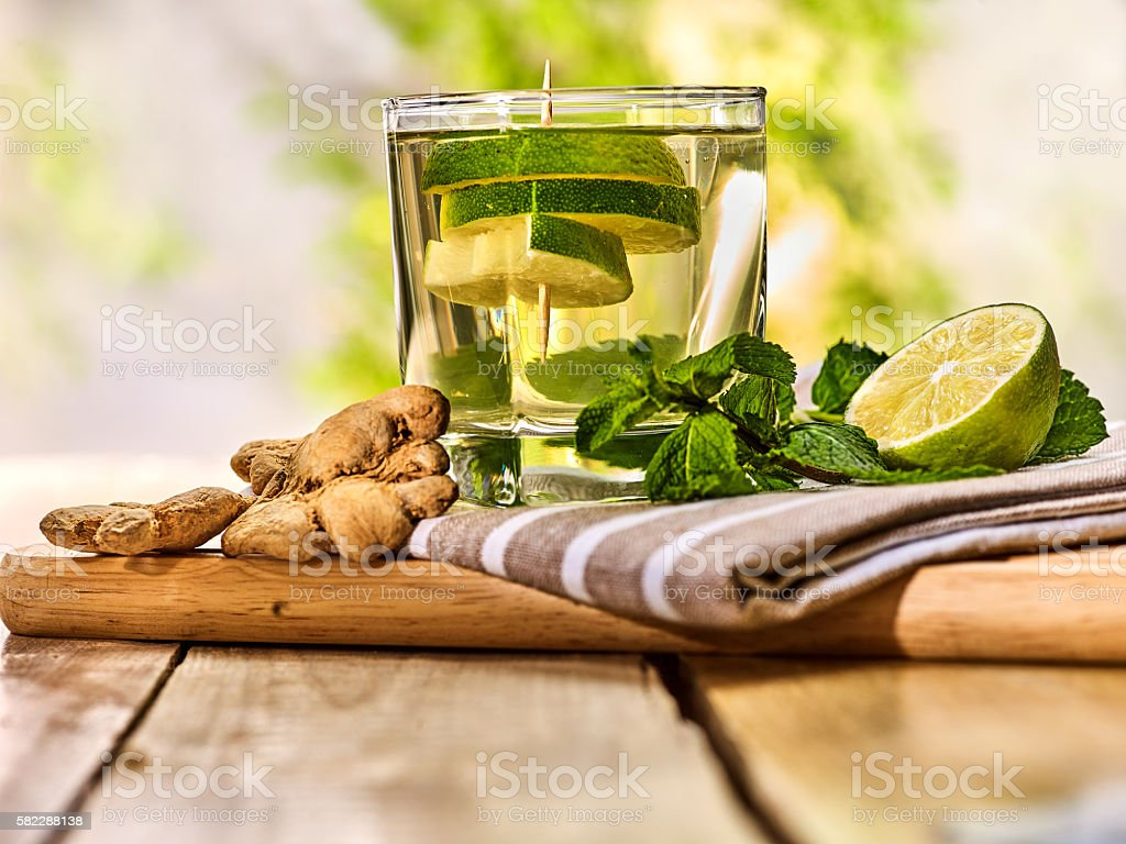 Glass with green transparent lime drink and ginger . stock photo
