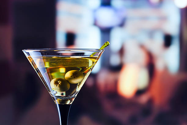 glass with martini and green olives stock photo