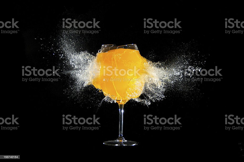 Glass with orange juice explosions at the black background stock photo