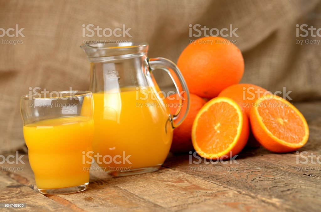 Glass with orange juice, jug with fresh juice and pile of oranges in the background on wooden table royalty-free stock photo