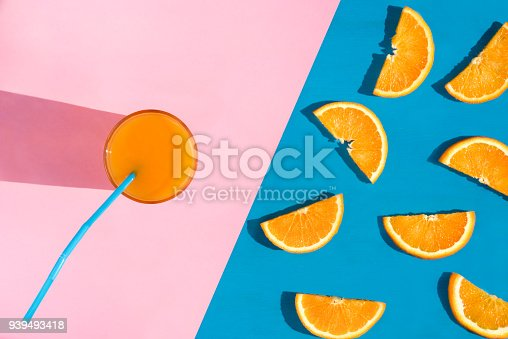 Summer image from a high angle view with a glass of healthy orange juice and a multitude of orange slices