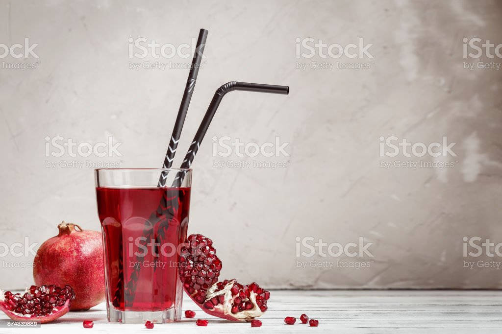 Glass with pomegranate juice and fresh fruit stock photo