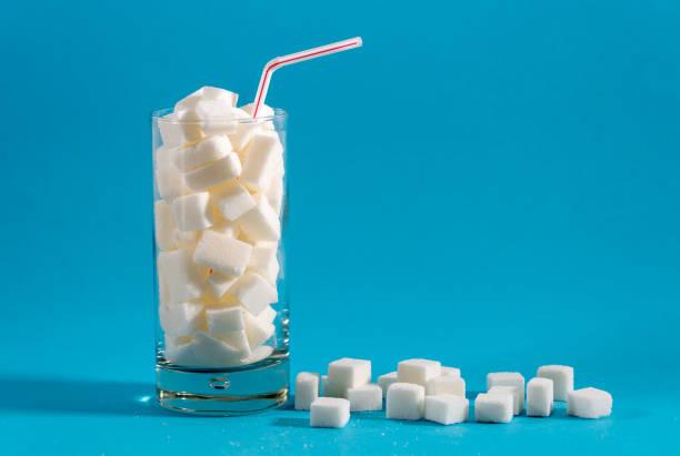 빨간 줄무늬 짚으로 유리 파란색 배경에 설탕 조각으로 가득합니다. 정크 식품, 건강 하지 못한 다이어트, 상쾌한 음료, 영양 개념에 설탕. - 설탕 뉴스 사진 이미지