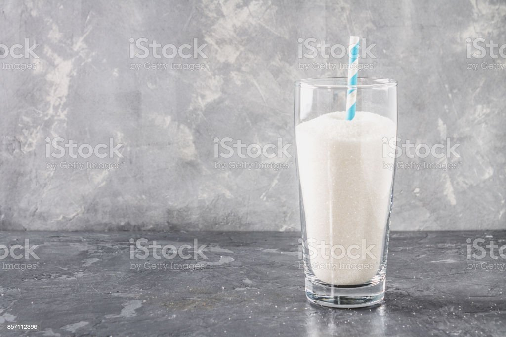 Glass with sugar sand is an unhealthy diet. The contents of sugar in sweet soda. stock photo
