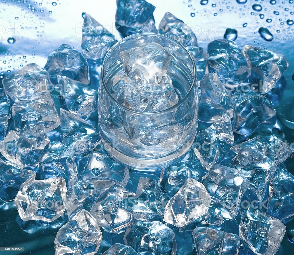Glass with water and ice over blue royalty-free stock photo