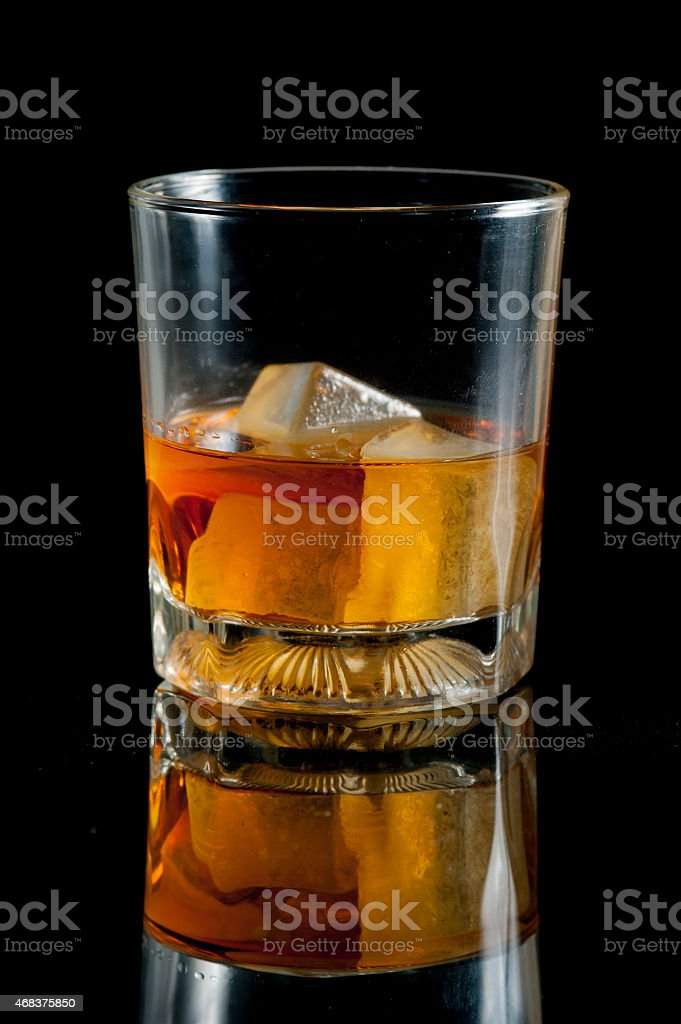 glass with whiskey against a black background stock photo