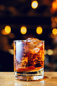 istock Glass with whiskey and ice cubes on the bar with bokeh on background. 1251676545