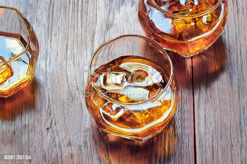istock Glass with Whiskey on table rustic wooden background, top view 638139134