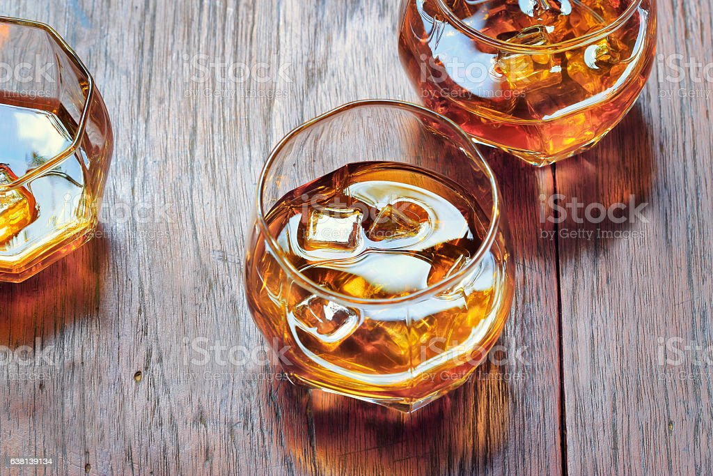 Glass with Whiskey on table rustic wooden background, top view stock photo