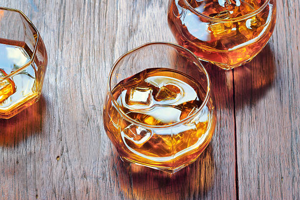 glass with whiskey on table rustic wooden background, top view - whiskey stock photos and pictures