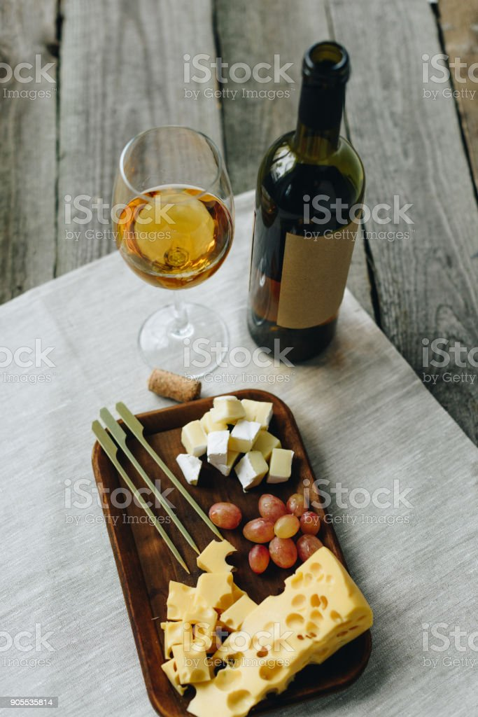 Glass with wine and plate with cheese and grapes stock photo