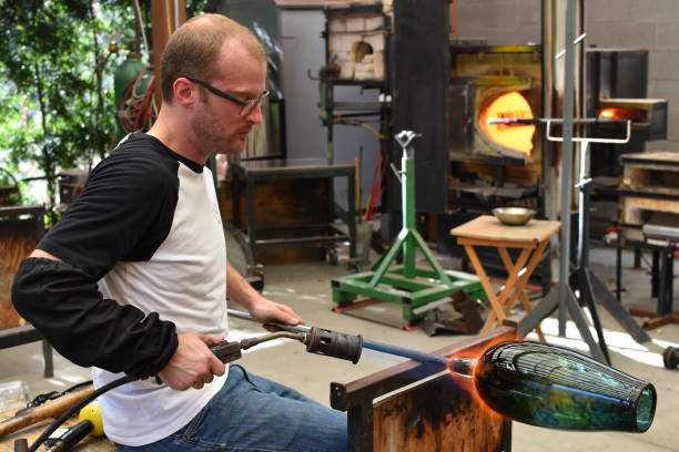 glassblower heating a finished piece of glass with a torch - steven harrie stock photos and pictures