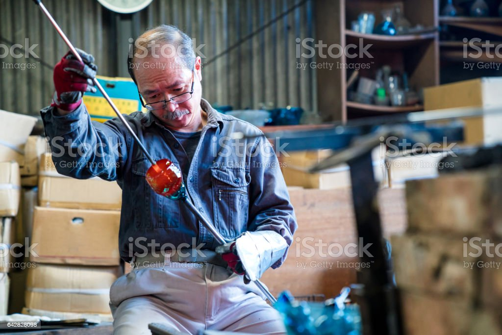 Glassblower inspecting his work stock photo
