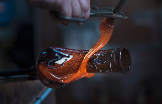 Glassblowing worker cutting liquid glass