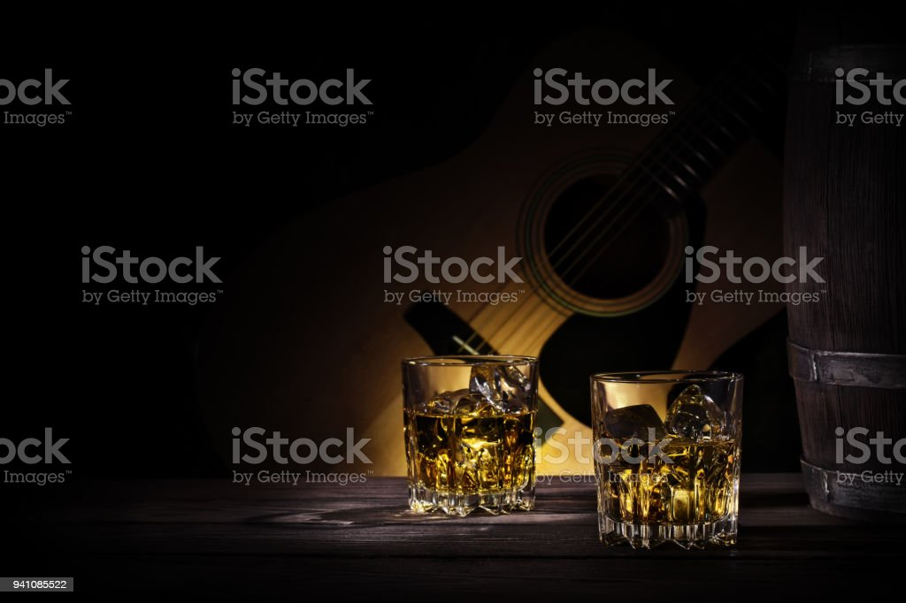 Glasses and barrel of whiskey on background of guitar stock photo