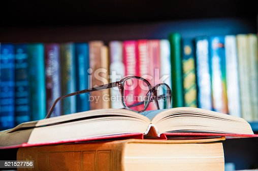 istock glasses and book on background bookcase 521527756