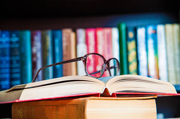glasses and book on background bookcase - literature stock pictures, royalty-free photos & images