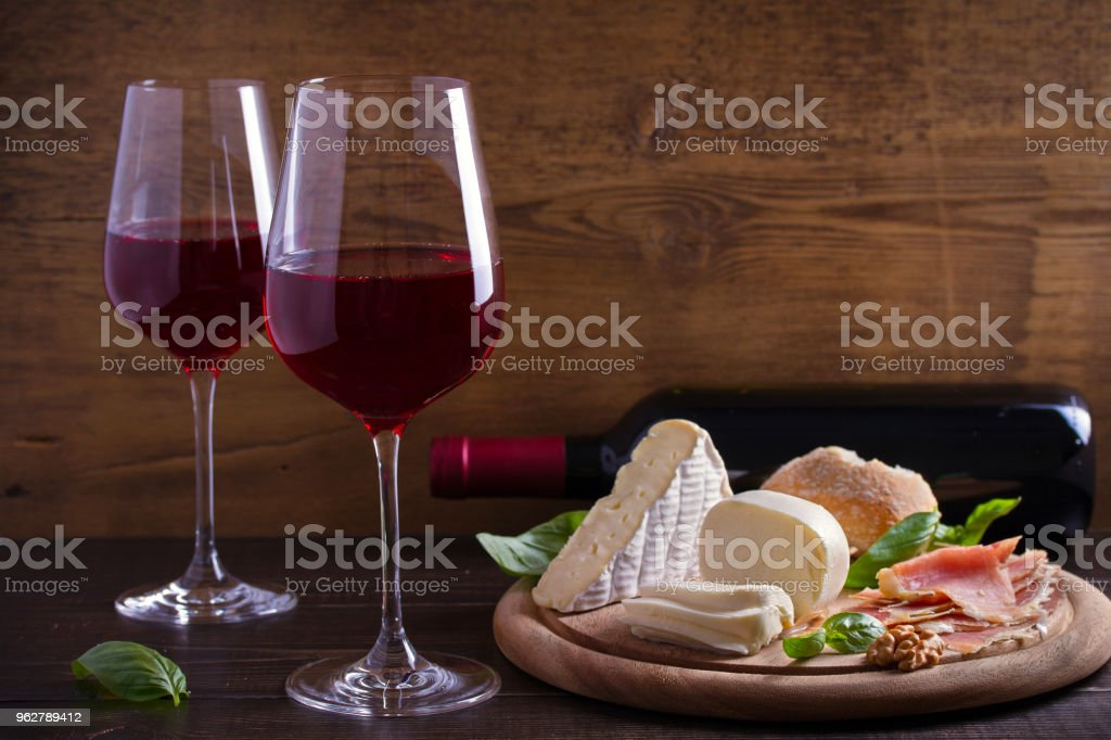 Glasses and bottle of wine with cheese, bread, nuts and jamon or prosciutto on dark wooden background - Foto stock royalty-free di Alchol