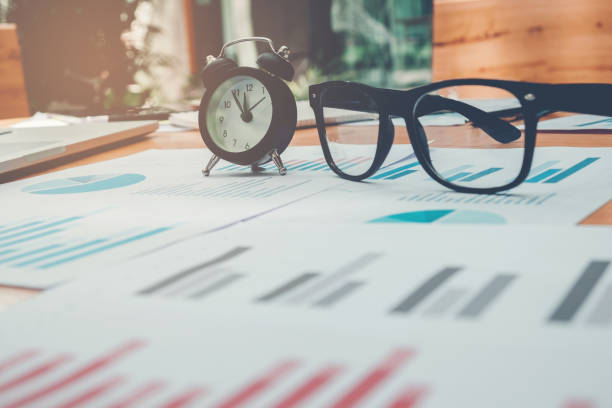 Glasses and clock on the business paper. Report chart stock photo