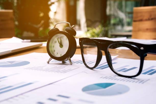 Gafas y el reloj en el papel de la empresa. Tabla de informe - foto de stock