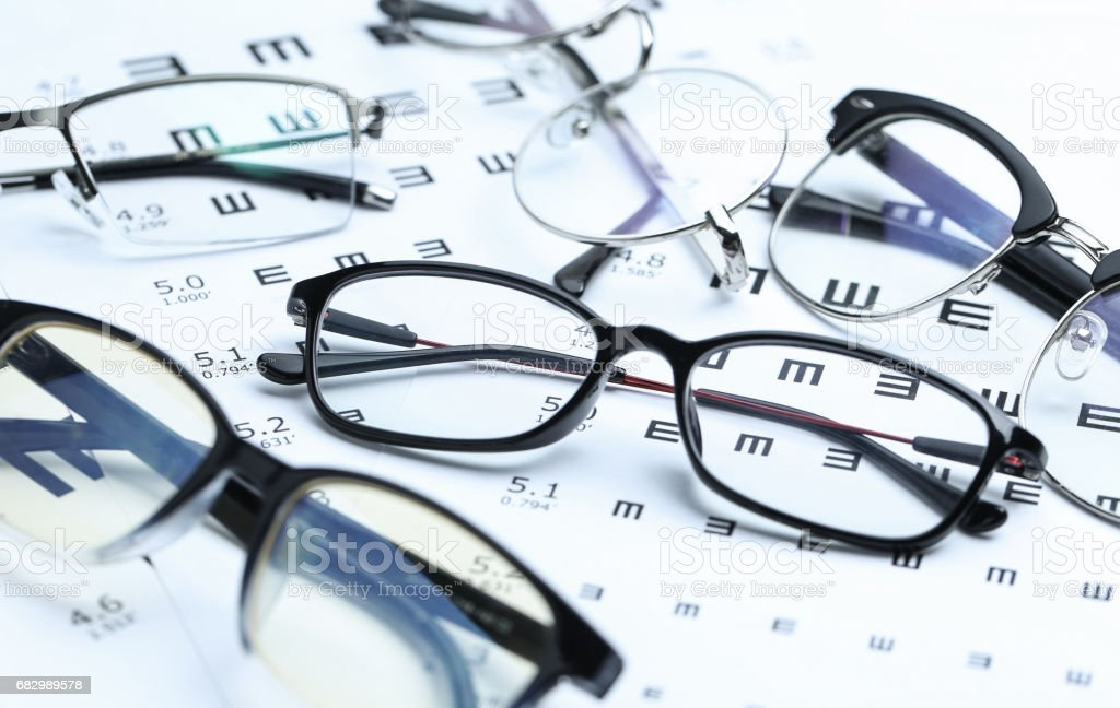 Glasses and eye chart on white background foto de stock royalty-free
