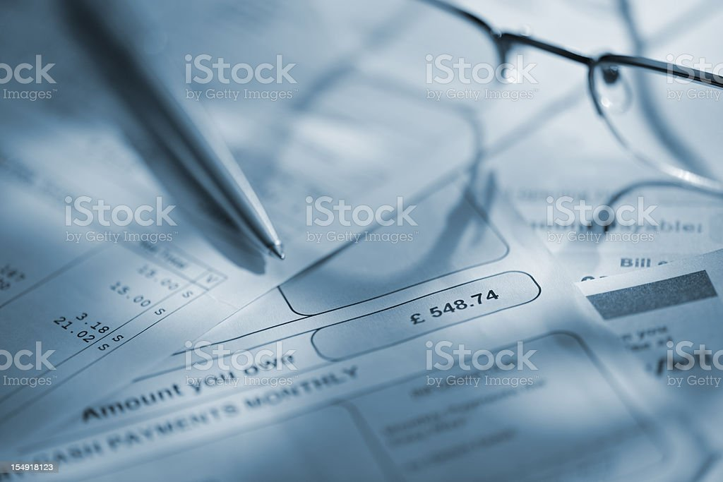 glasses and pen on household bills royalty-free stock photo