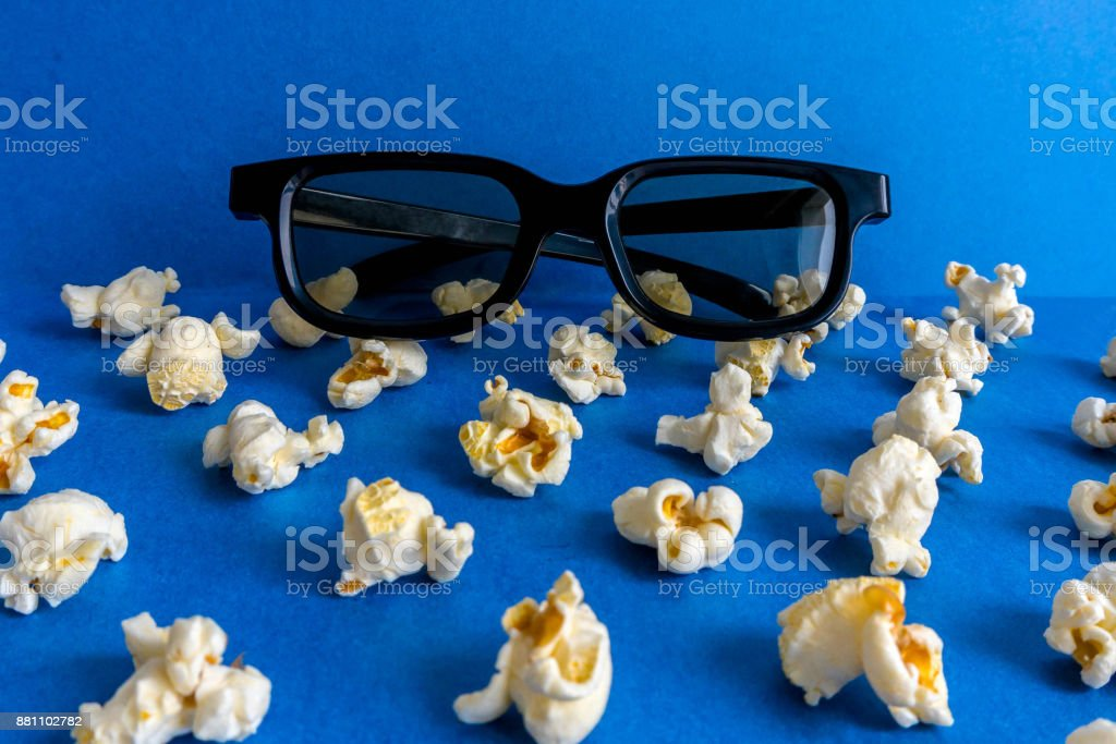 3D glasses and popcorn on a blue background. stock photo