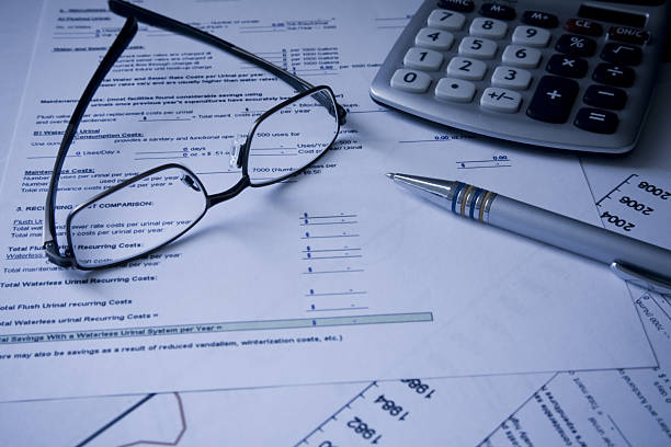 glasses, calculator and pen on financial cost documents - social security check stock photos and pictures