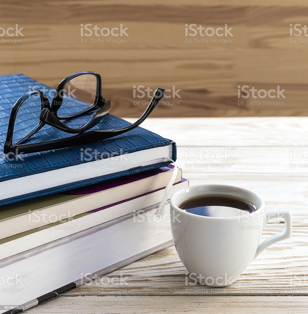 Glasses, cup of hot coffee and book on wooden table stock photo