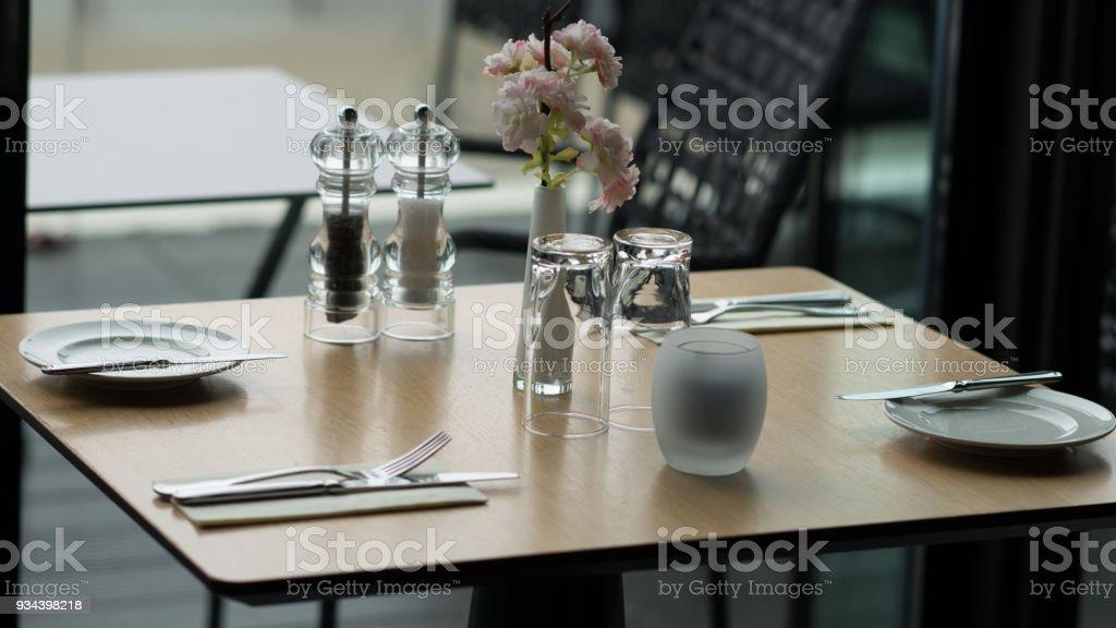 Glasses, flower fork, knife served for dinner in restaurant with cozy interior stock photo