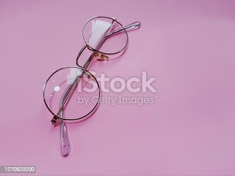 Glasses for sight on a pink background. View from above. Reflection of light from lenses. Copy space.