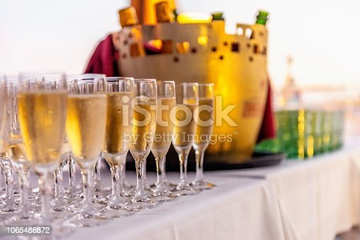 Glasses full of champagne arranged on table in a row at luxury event.