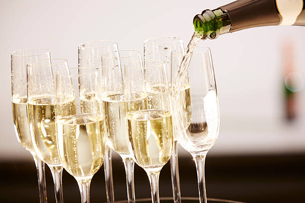 Glasses full of champagne on a tray Champagne drinks being poured on a tray epernay stock pictures, royalty-free photos & images