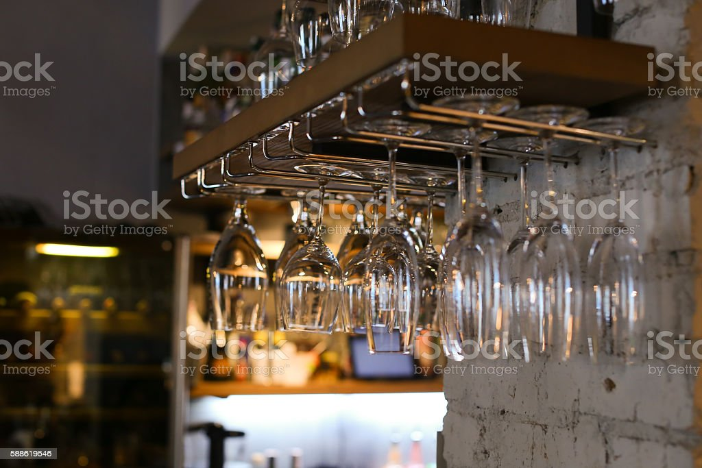 Glasses hanging upside down in cafe restaurant wine stock photo