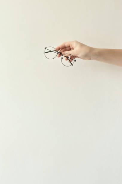 gafas en un marco de metal fino en las manos. - lifestyle color background fotografías e imágenes de stock