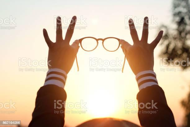 Glasses in woman hands on sunset background picture id862164056?b=1&k=6&m=862164056&s=612x612&h=omm 10a tyzgc1vcpcbtdb0ix97c4qba cz4ldelzdu=