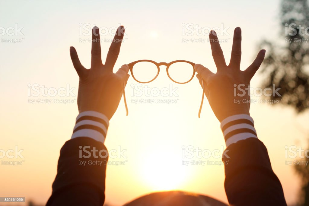 Glasses in woman hands on sunset background stock photo