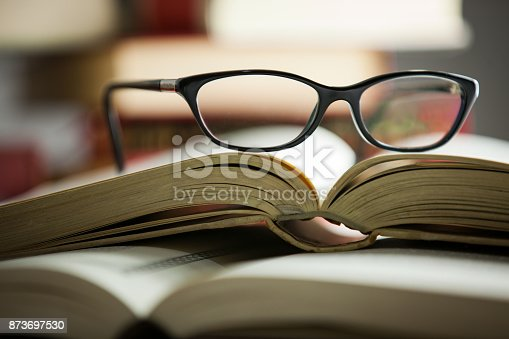 black glasses lies on a folded book in a shelf