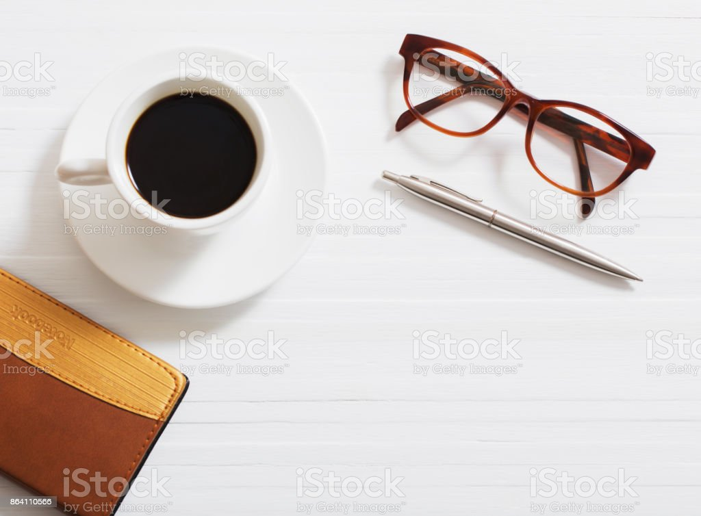 glasses, notebook, pen and cup of coffee on white wooden background royalty-free stock photo